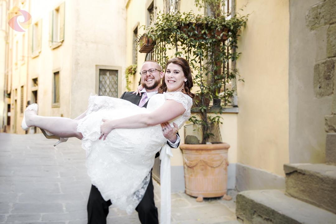 Lo sposo porta la sposa in braccio, entrambi ridono, in uno scorcio del borgo di Cortona