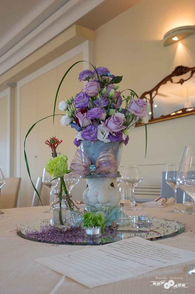 A centerpiece inspired by Alice in Wonderland, by Lewis Carroll, with a white rabbit with a top hat and pink and purple roses