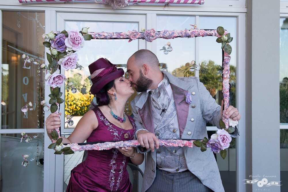 Happy spouses in victorian age fashion, kissing behind a pink rose frame