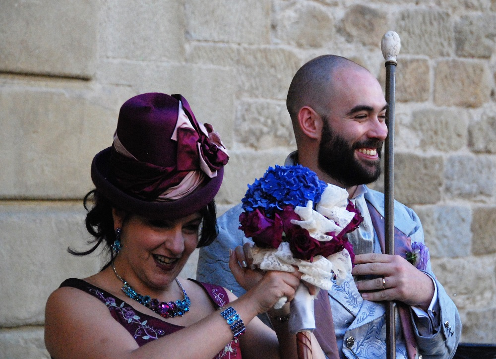 Happy Spouses wearing top hats, with a bouquet on a stick and a walking stick.