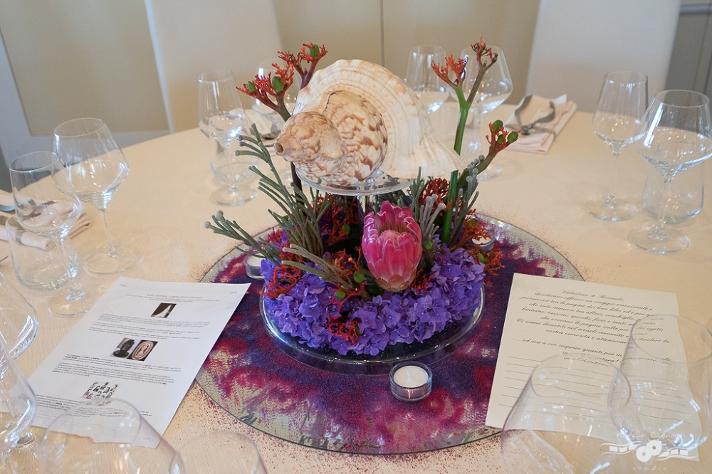 A centerpiece inpired by Twenty Thousand Leagues Under the Seas, by Jules Verne, with a huge seashell on top of a bed of violet flowers