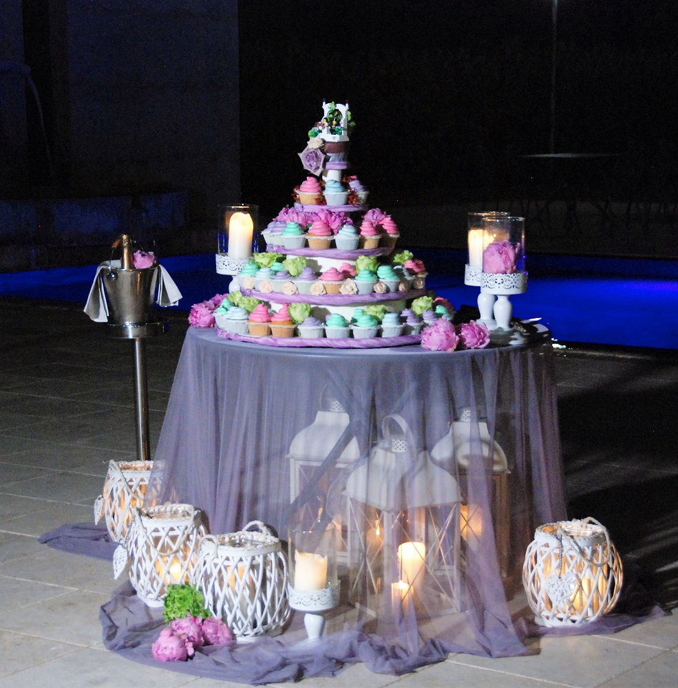 A wedding cake made of colorful cupcakes, surrounded by lamps and candles on a table with sheer tablecloth, with a lego cake topper
