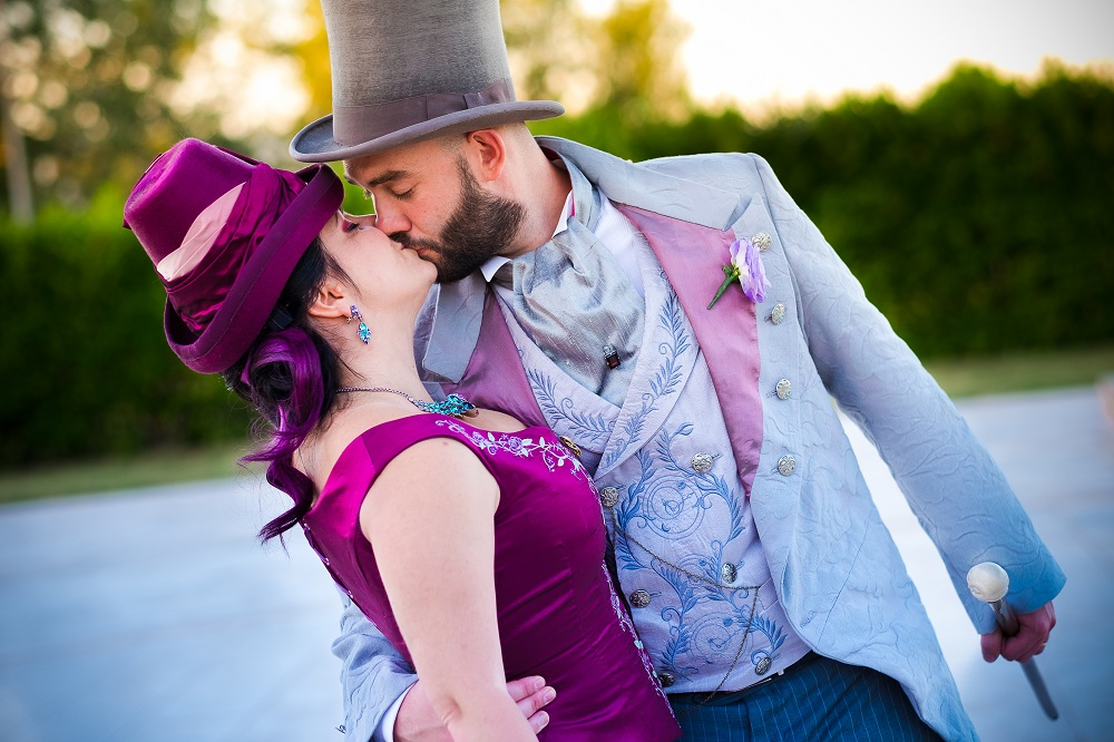 Spouses dressed in late victorian era fashion, sharing a passionate kiss in their top hats.