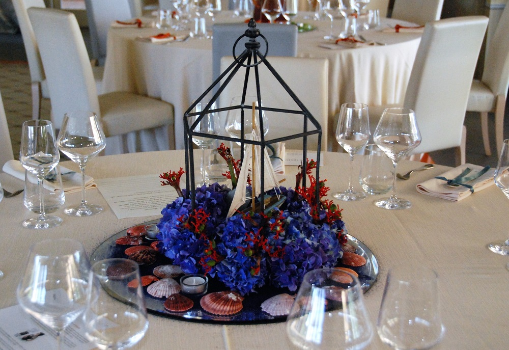A centerpiece inspired by Moby Dick, by Herman Melville, with a sailboat inside an iron lamp frame, on a bed of seashells and blue and red flowers
