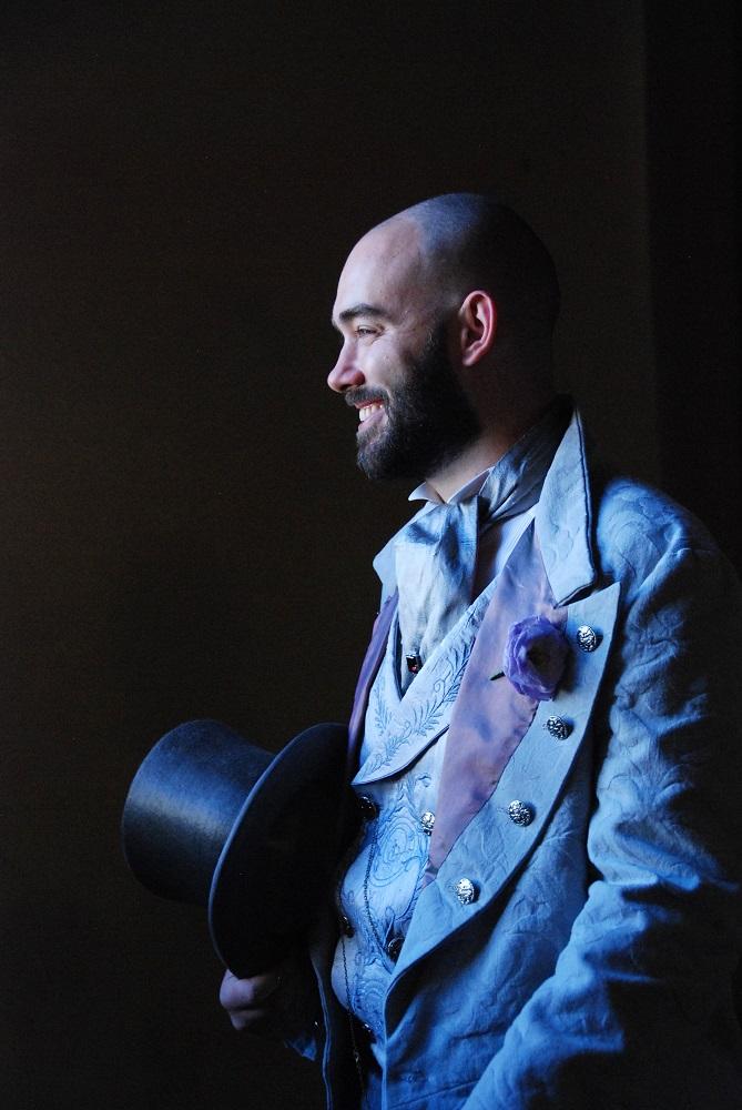 Smiling victorian groom holding an elegant top hat