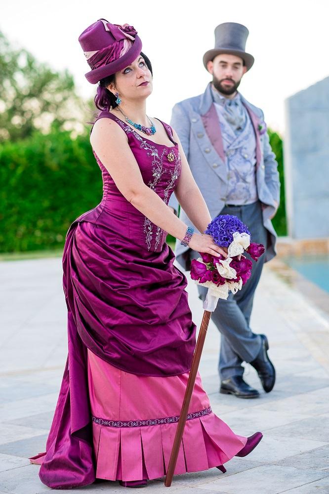 Sposi in stile tardo vittoriano, abito da sposa fucsia e rosa, abito da sposo grigio