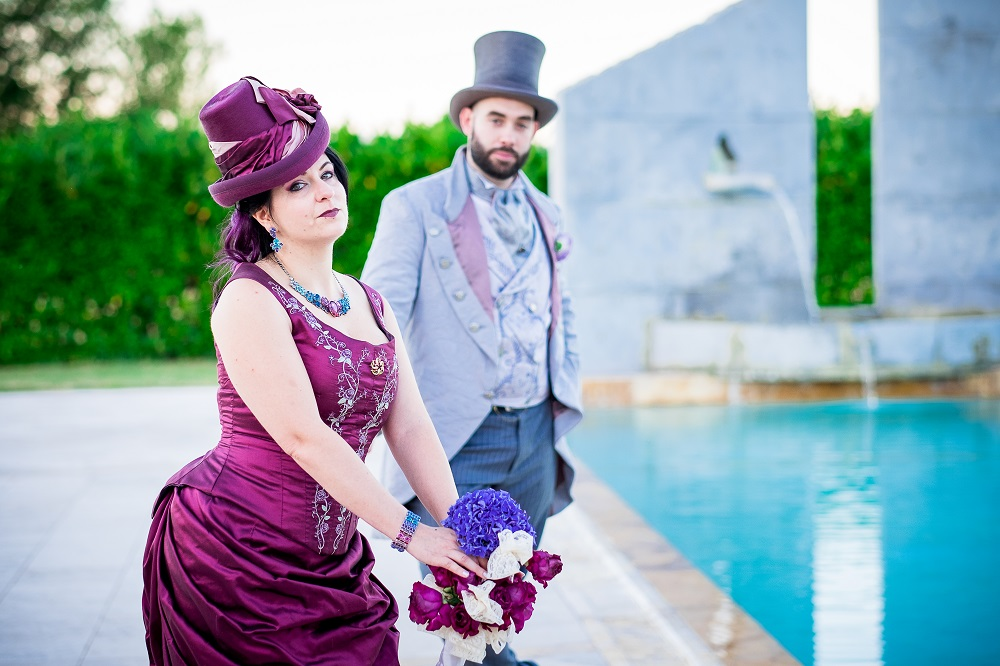Spouses dressed in late victorian era fashion, in front of a monument