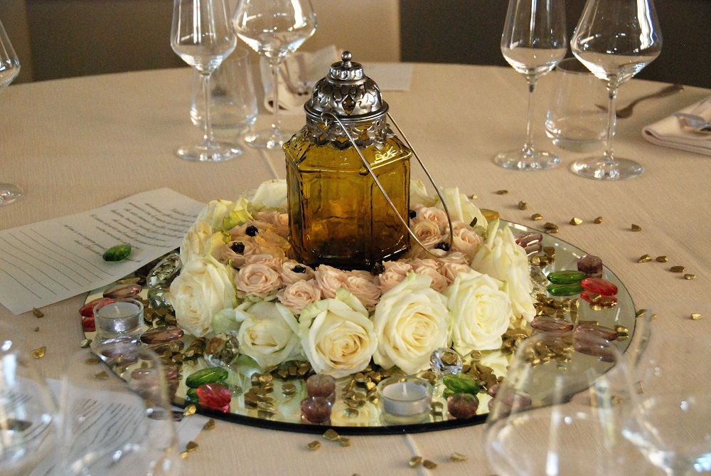 A centerpiece inspired by The Count of Monte Cristo, by Alexandre Dumas, with an amber coloured lamp inside a ring of white and pink roses