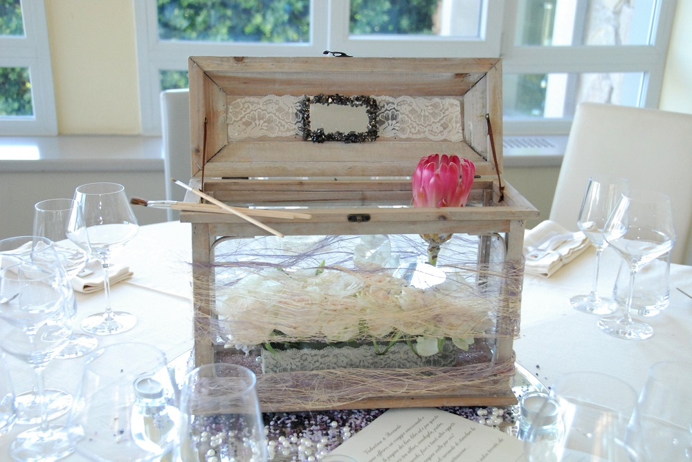 A centerpiece inspired by The Potrait of Dorian Gray, by Oscar Wilde, with white roses in a glass display