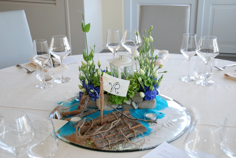 A centerpiece inspired by Tom Sawyer, by Mark Twain, with a raft made of bark on white and light blue sand.