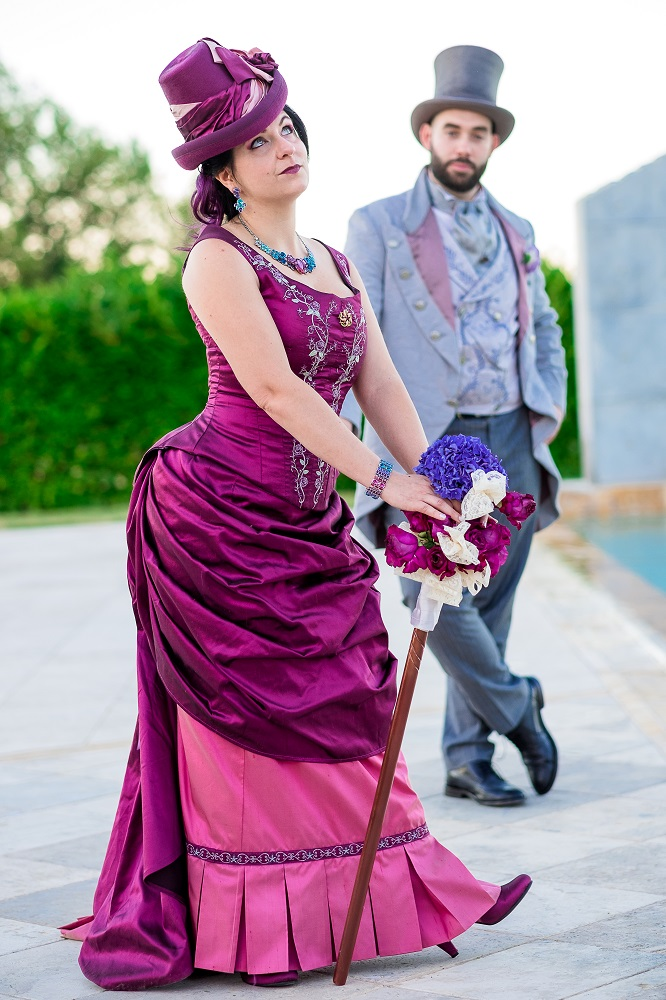 A full figure photo of a victorian bride in a hot pink dress, with her bouquet on a stick, with the groom in the background in his top hat