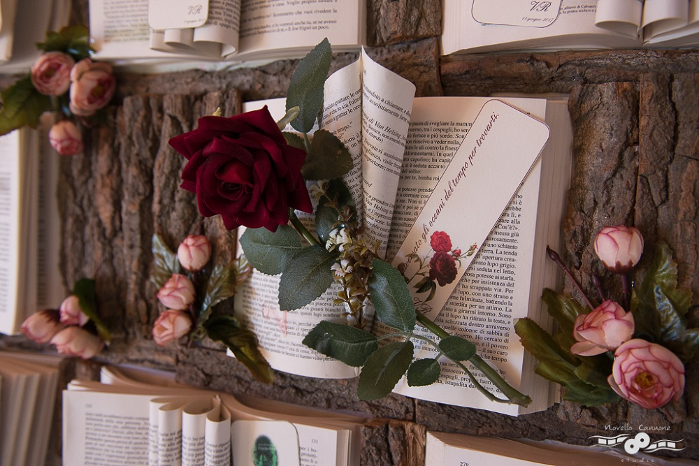 Close up of a Tableau de Mariage made with victorian literature, with a red rose on top, on a sheet of tree bark