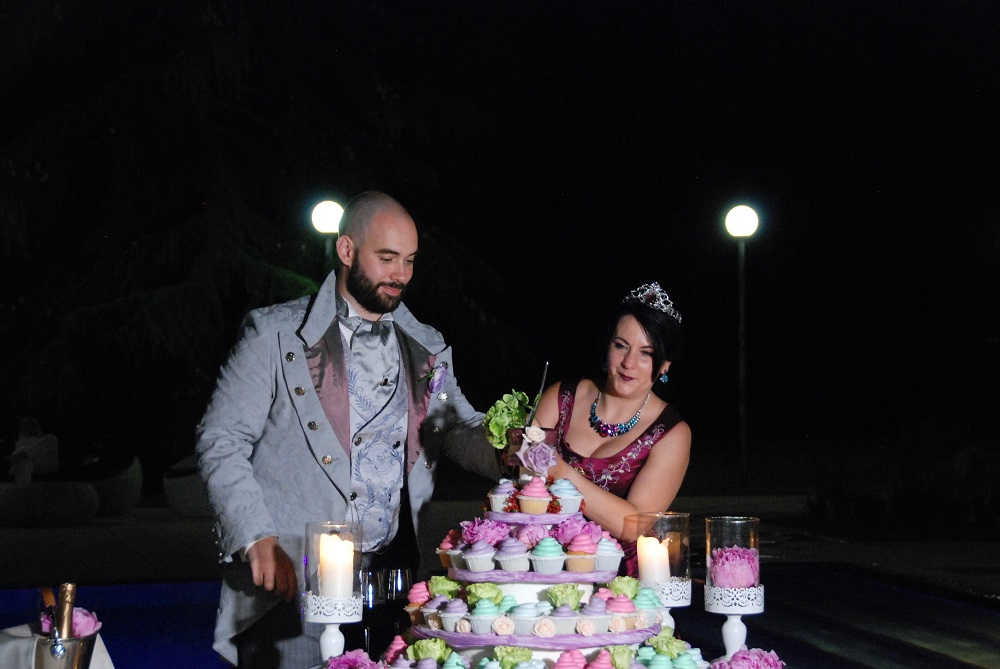 Cutting of the cake, with the victorian dressed spouses cutting the top of a cake made of colorful cupcakes, surrounded by candles