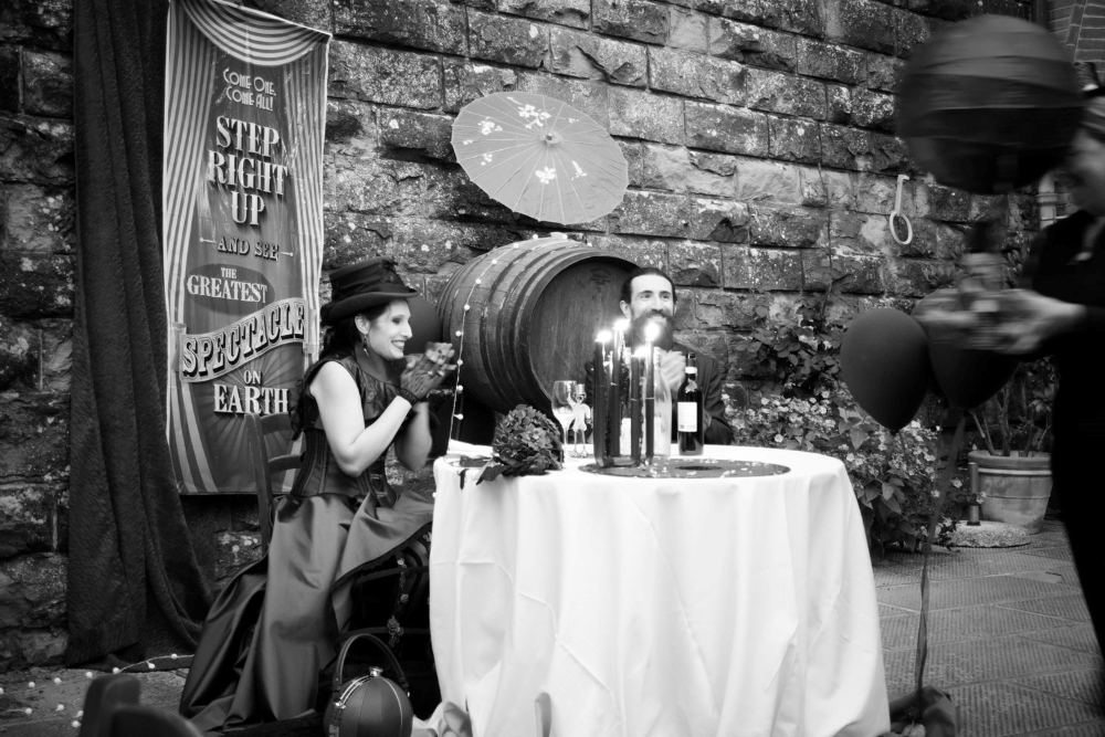 A black and white photograph of two laughing spouses at a table, with a victorian circus banner and a wine barrel behind them