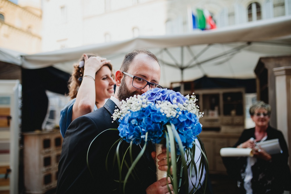 Happy groom holding a blue and white bouquet, at a city hall wedding.
