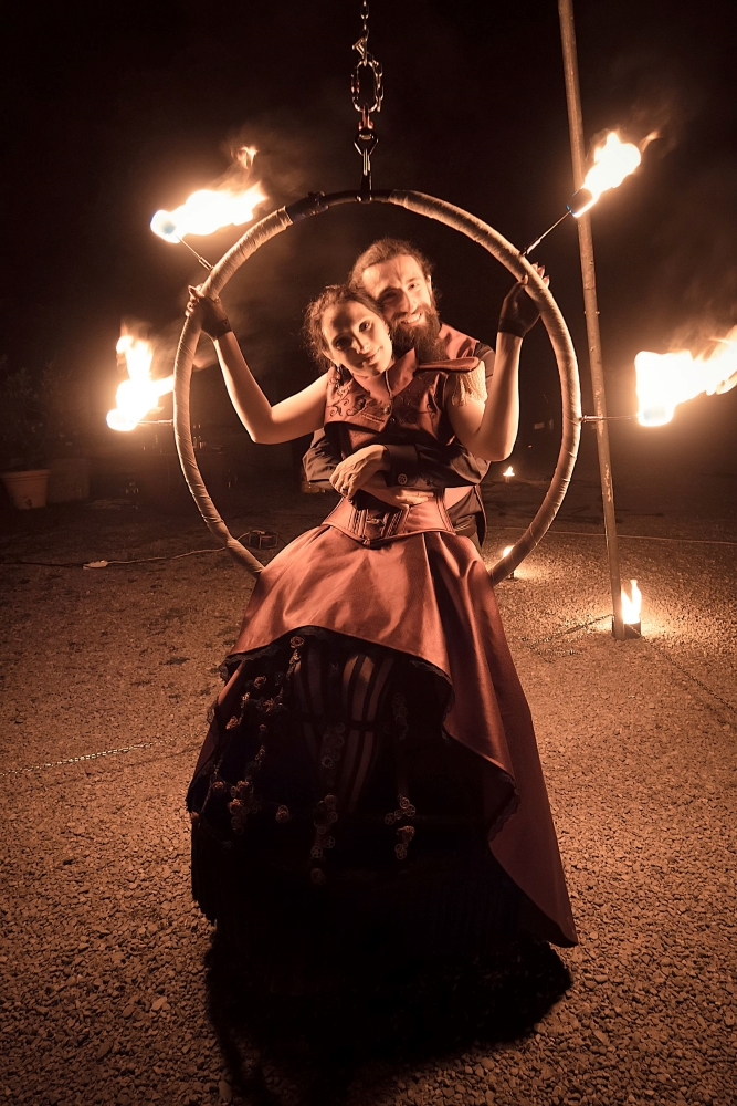 A full figure photo of spouses in gothic fantasy clothing, posing inside a fire circle and smiling