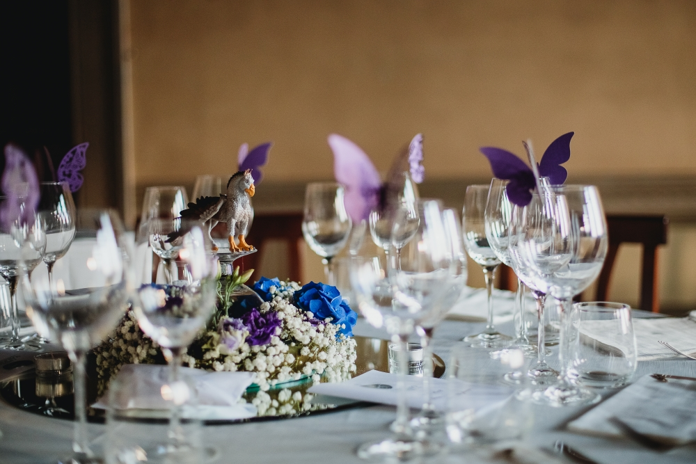Centerpiece with an action figure of a gryphon on a raised platform, with violet butterflies on the rim of crystal glasses
