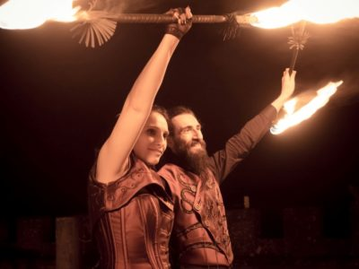 Smiling bride and groom in steampunk style clothing, posing with burning fire show equipment