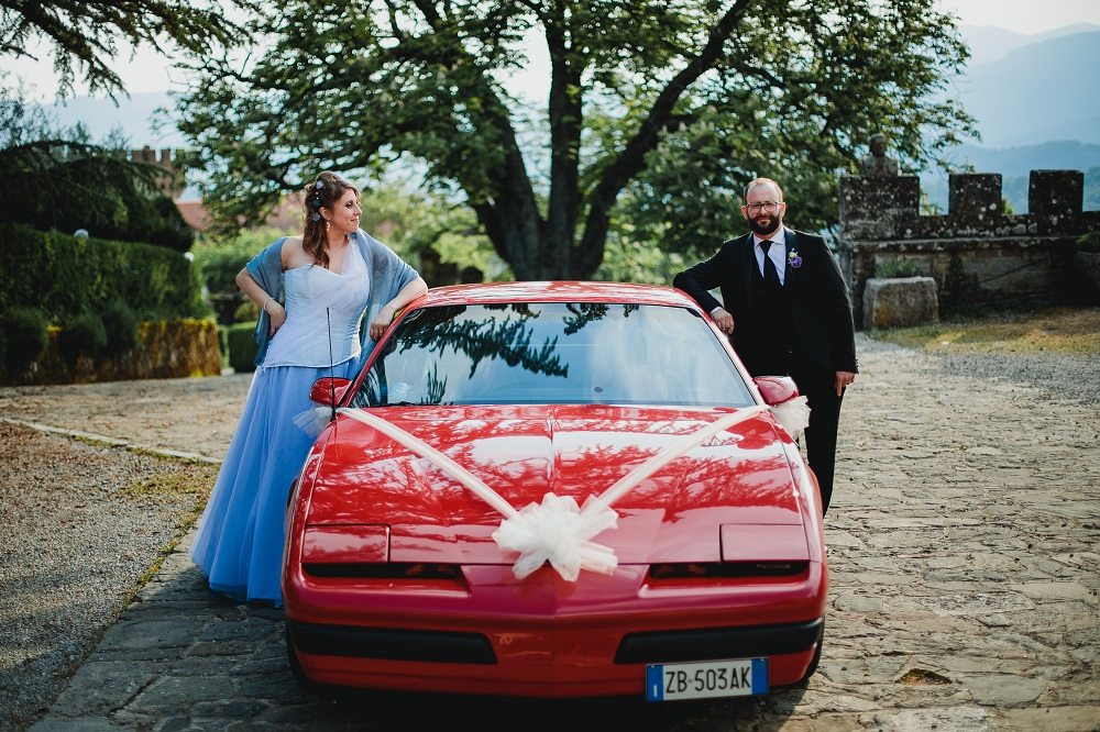 Smug bride and groom leaning on a sports car, at a castle wedding