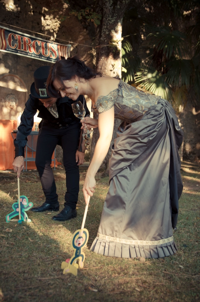 Steampunk dressed woman and man, playing victorian games at an open air wedding