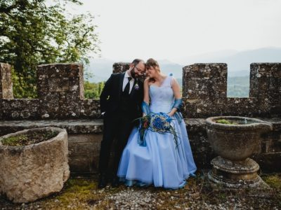 Happy spouses in a castle wedding in tuscany, smiling while sitting on the castle walls
