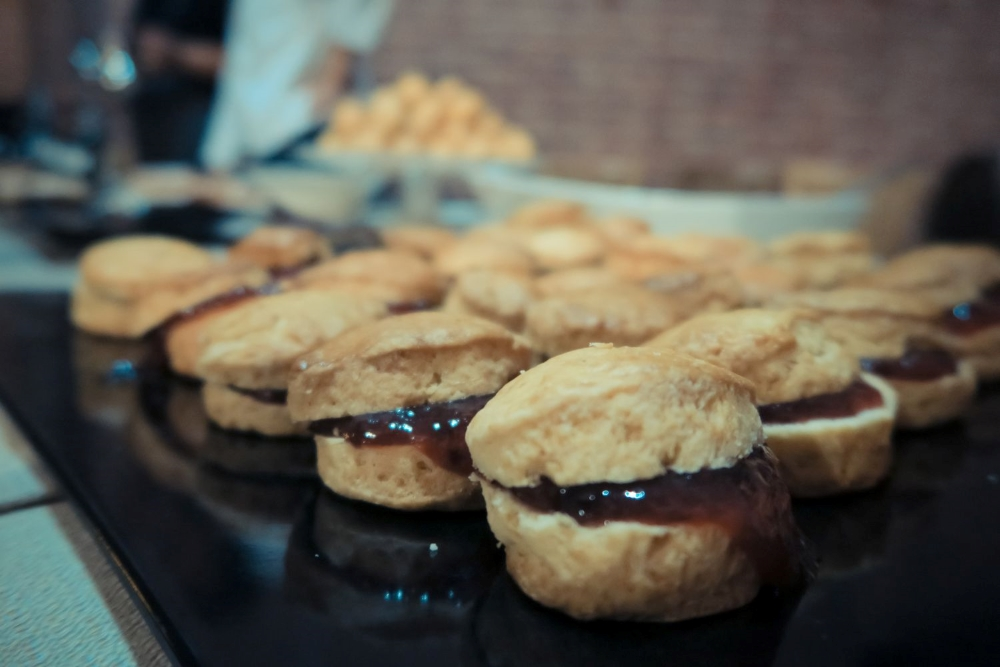 A black tray full of small english tea scones with jam at an open air ceremony