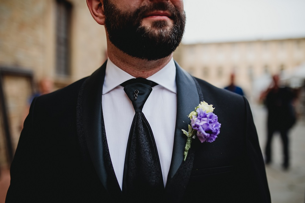 The groom at a civil hall wedding, with his violet buttonnière on and a black damask pattern tie and jacket