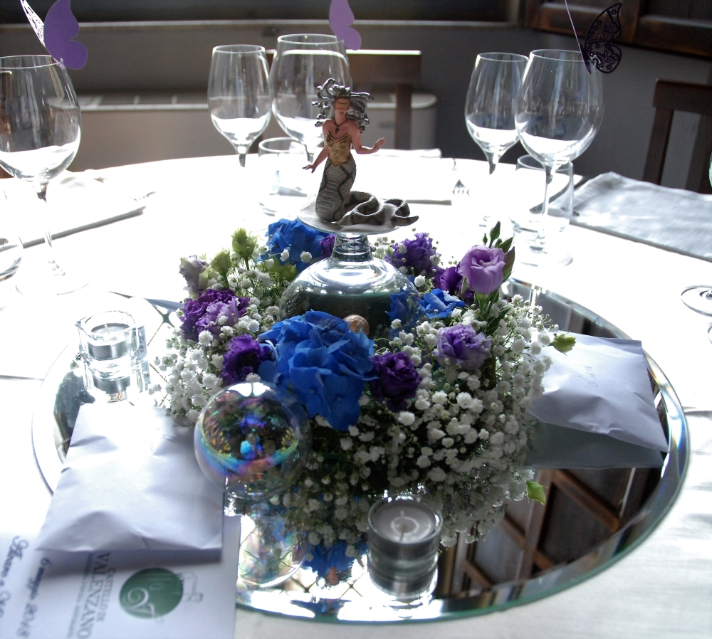 A centerpiece made with an action figure of a mermaid, surrounded by purple decorative butteflies on the rim of crystal glasses, with rainbow spheres