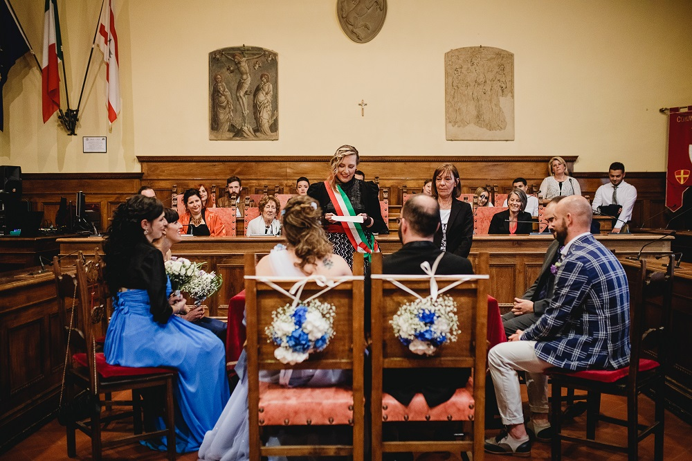 A photography of a stylish city hall wedding, the happy spouses are shot from behind, sitting, with a clear view of the officiant and witnesses and invitees