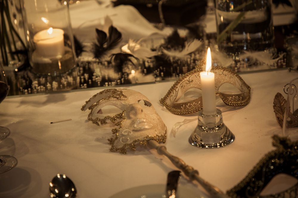 Centerpiece detail, with mirrors, black feathers, candles and two white and gold masks with a burning candle.