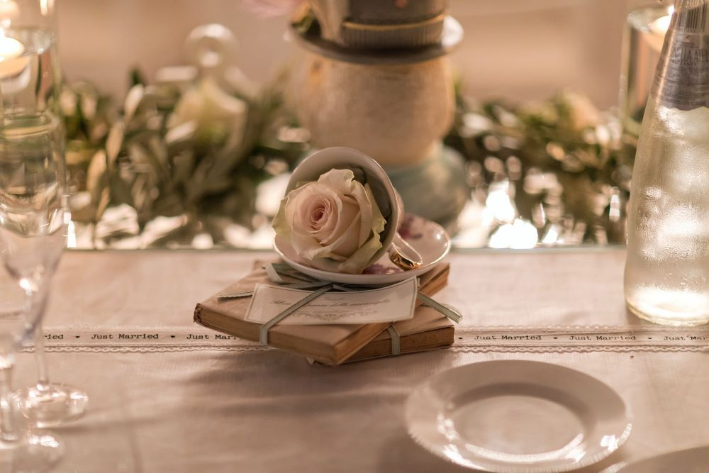 A pink rose in a vintage teacup for an Alice in Wonderland wedding decor