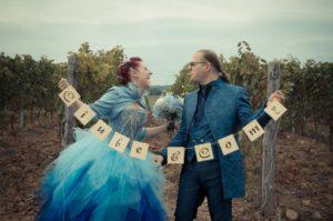 Sposi in blu che ridono e si fanno linguaccia, sullo sfondo di una vigna