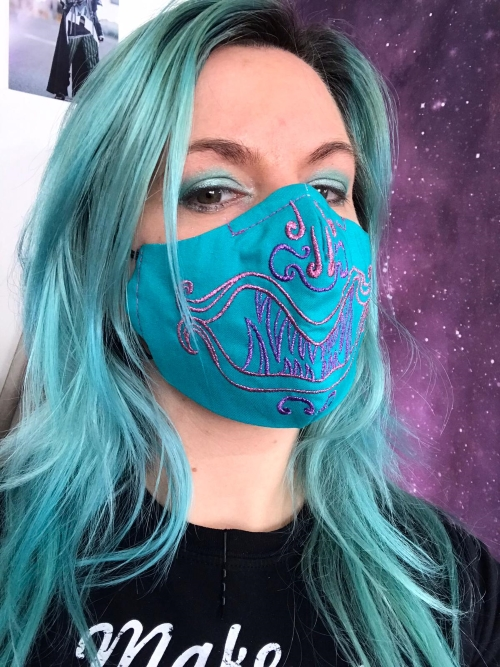 A girl with green/blue hair wearing a blue mask with a purple embroidery that resembles a monster.