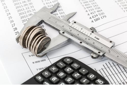 Calibro che prende lo spessore di un po' di monetine, una calcolatrice e un foglio con numeri a caso.