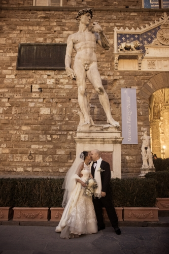 Spouses kissing under the statue of the David of Michelangelo in Florence