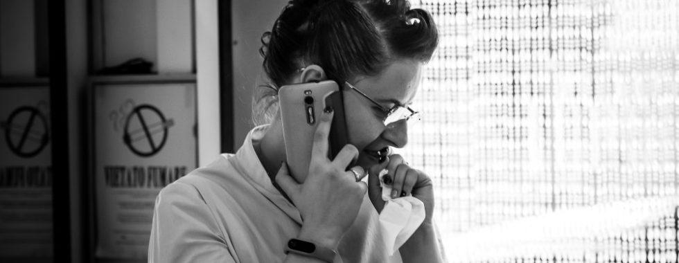 Foto in bianco e nero di una WP pensierosa al telefono che risolve imprevisti di nozze