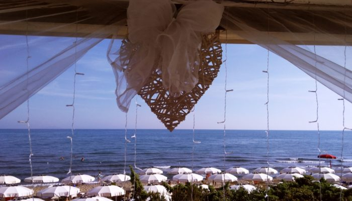 A beautiful view of the Seaside of Castiglione della Pescaia, Framed by tull, fairy lights and a heart, as you'd see on August 15th.