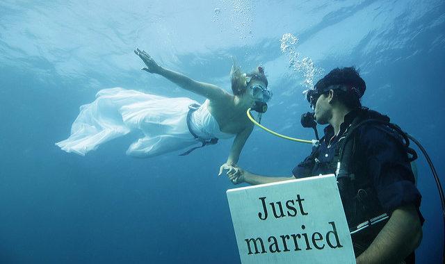 Foto di due sposi sott'acqua, lo sposo ha un cartello