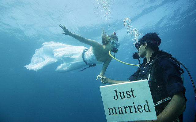 Elopement - Scuba spouses, the groom holds a