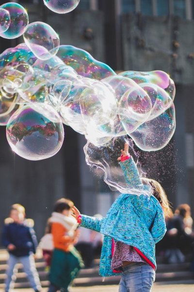 A child plays with giant soap bubbles