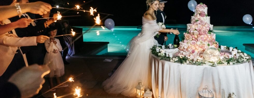 The spouses in their perfect venue, cutting the cake in front of the swimming pool with people all around with magic sparkles