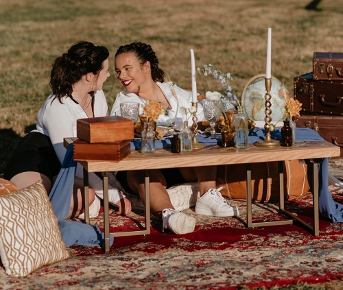Two women in front of a beautifully decored table, with candles and wooden boxes - Micro-weddings