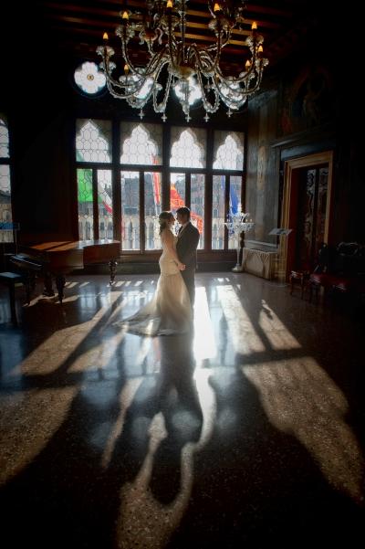 Una coppia, da sola, nel salone di un bellissimo hotel con il sole che filtra dalle grandi vetrate alle loro spalle