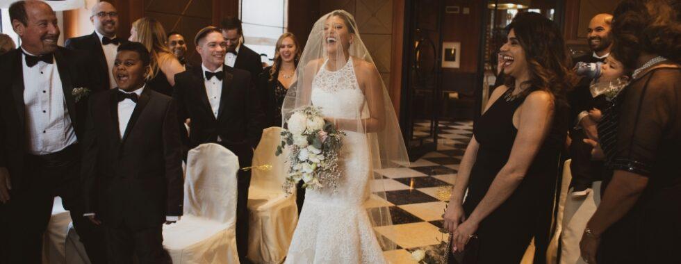 Micro-wedding del 2019, con la sposa che passa tra gli invitati ridendo nella sala della cerimonia