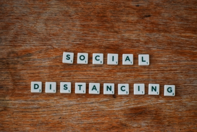 """Wooden table with Scrabble tiles that write """"Social Distancing"""""""