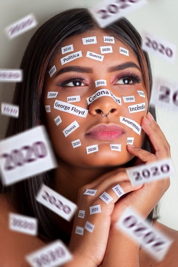 A woman of colour with light make up looking up and with strips of white paper with written words on her face. Words include: Coronavirus, George Floyd, and, repeatedly, 2020.