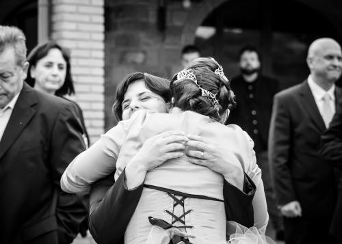 Una sposa di spalle che abbraccia stretta un'amica che ricambia l'abbraccio
