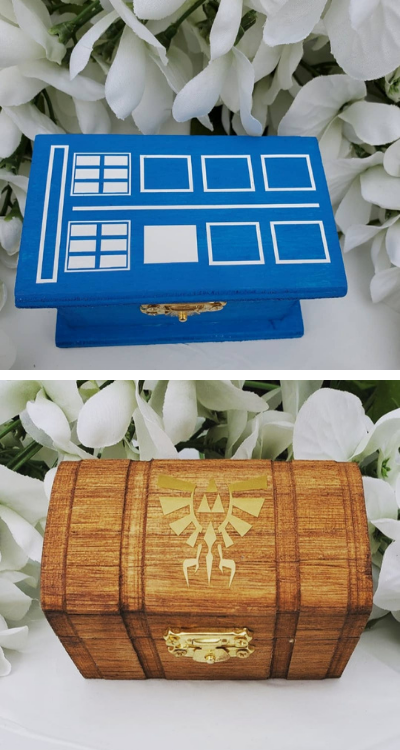 Two wooden boxes. The one on the top is Tardis-blue and decorated as a TARDIS, the other is wooden-coloured and there's the Legend of Zelda's logo on
